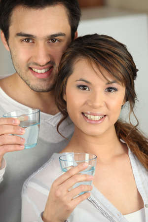 Enthusiastic man and woman with glasses of water photo