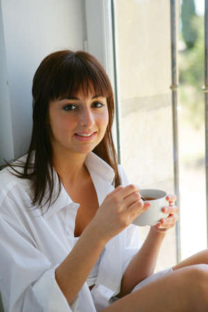 young woman drinking coffee at home photo