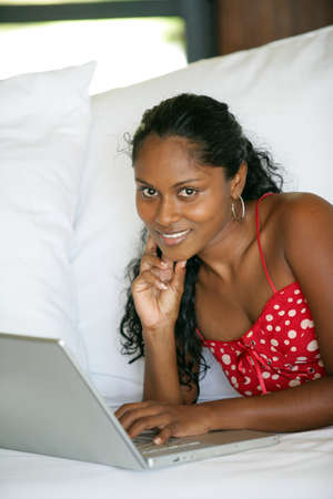 computer equipment: beautiful Afro-American woman lying on the couch with her laptop