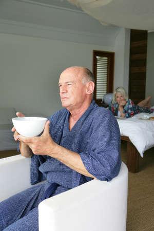chew over: Man having breakfast in front of a window