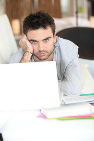 holgaz�n: Aburrido hombre usando la computadora port�til Foto de archivo