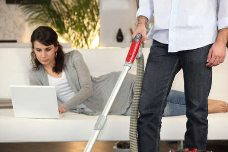 chore: Man vacuuming and a woman working on her laptop