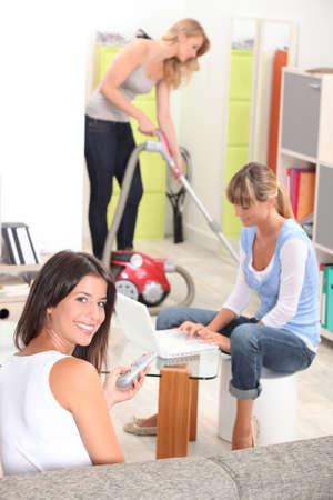 mujer arrodillada: Tres compañeros de casa femenino de limpieza