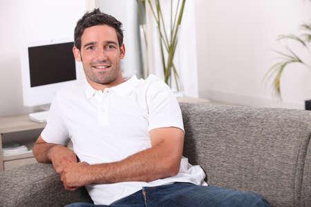 35: Hombre de 35 a�os sentado en un c�modo sof� Foto de archivo