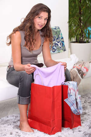 Brunette looking through bags of shopping photo