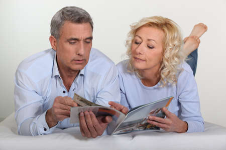 age 50 55 years: Middle-aged couple leafing through a brochure