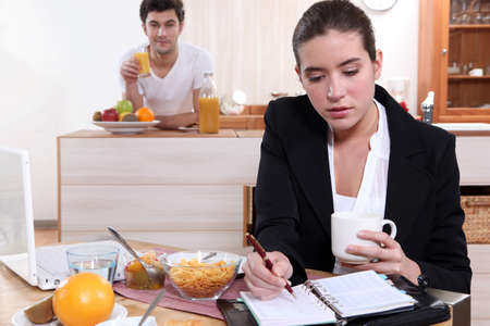 hurried: Couple eating breakfast separately Stock Photo