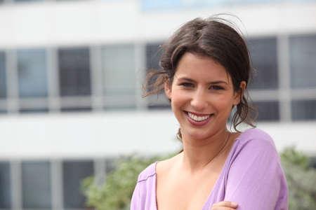 amabilidad: mujer joven y sonriente delante de un edificio