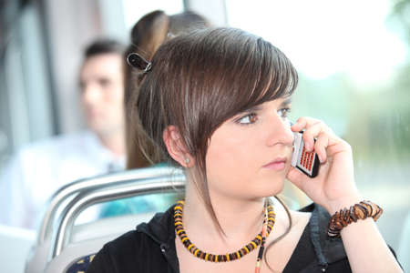 15 18: Trendy young woman using her cellphone on a tram