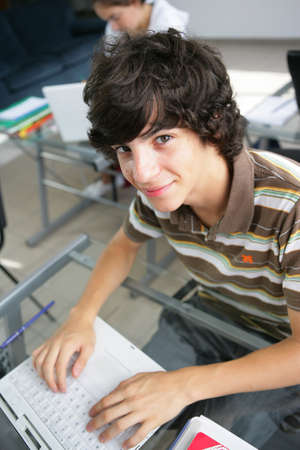 15: Teenager using a laptop at his schooldesk