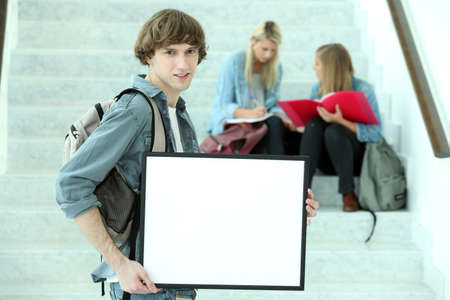 coursework: College student holding a black framed board left blank for your image Stock Photo