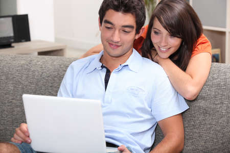 Couple watching film on laptop computer at home photo
