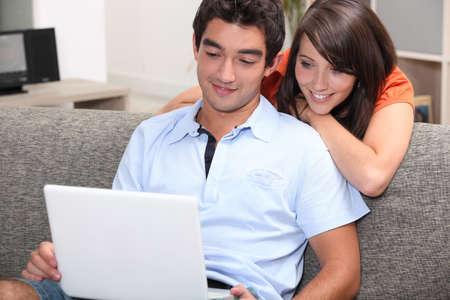 personas viendo tv: Pareja viendo la pel�cula en el ordenador port�til en casa Foto de archivo