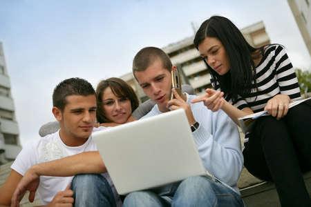 pareja de adolescentes: Cuatro adolescentes que usan ordenador portátil Foto de archivo