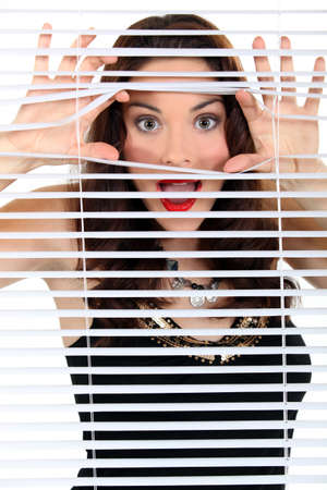 blinds: Woman peeking through blinds Stock Photo