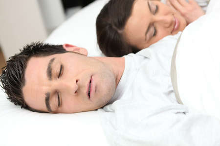 Man sleeping deeply next to his girlfriend photo