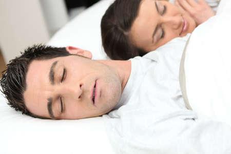 Man sleeping deeply next to his girlfriend photo