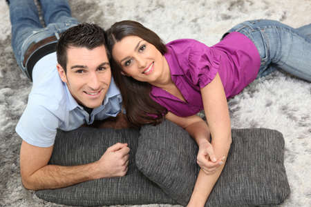 25 35: Couple laying on cushions on the floor Stock Photo