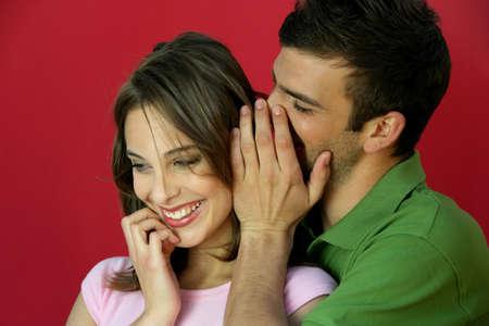 Man telling secret to woman photo