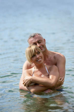 Middle-aged couple swimming photo