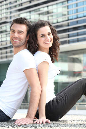 beau jeune homme: Couple assis dos à dos bâtiment extérieur