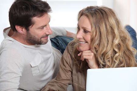 Couple on laptop looking into each other Stock Photo - 12057895