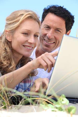 2 50: Couple looking at laptop outdoors.