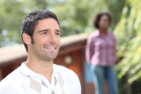 Man standing outside a log cabin with a woman out of focus in the background photo