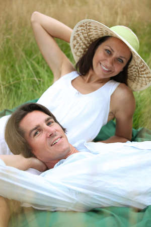 40 years old man and woman relaxing and  lying down in a meadow photo