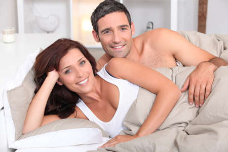 auburn hair: a couple reposing in bed in the morning