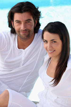 young couple smiling: Couple wearing white next to a pool Stock Photo
