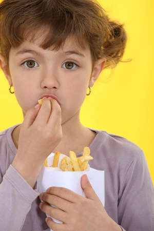 Young girl eating fries photo