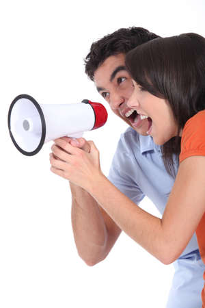 commotion: Young couple shouting into a loudspeaker