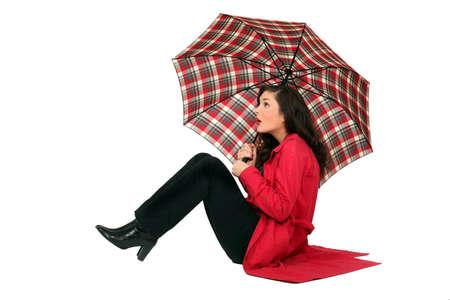 rain boots: Scottish woman sitting with umbrellas Stock Photo