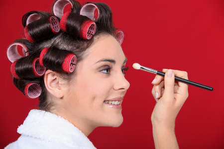 Woman with hair curlers applying make-up Stock Photo - 12057746