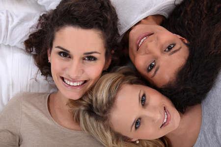 lay down: Three woman portrait. Stock Photo