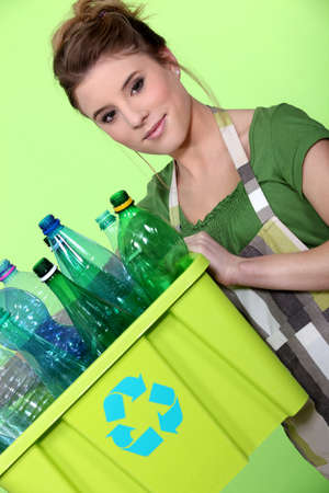 environmentally friendly: Young woman taking out the recycling