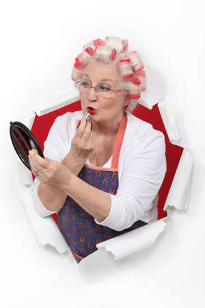 curlers: Elderly woman applying lipstick Stock Photo