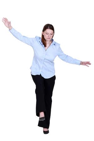 daredevil: Woman pretending to walk on tight-rope Stock Photo