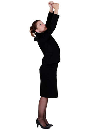 Businesswoman reaching upwards photo