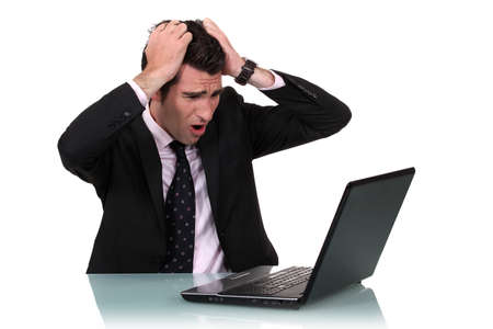 annoyance: A businessman pissed at his laptop.