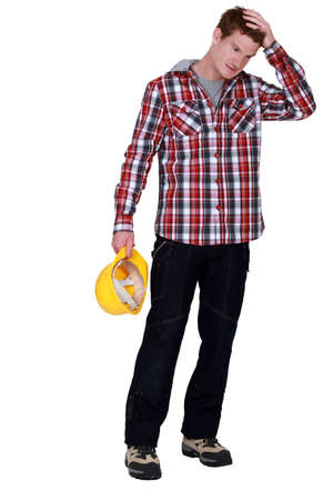 workman holding hard hat with hand on his head Stock Photo