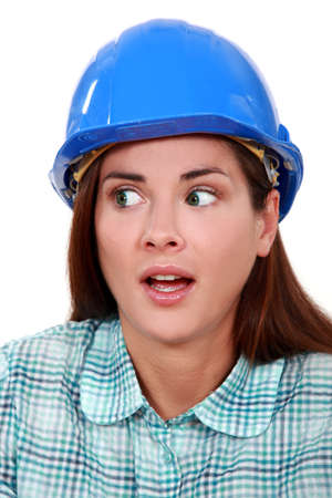 A portrait of a scared female construction worker. photo