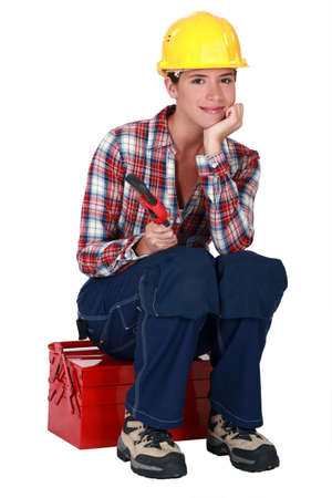 A female worker sitting on her toolbox. photo
