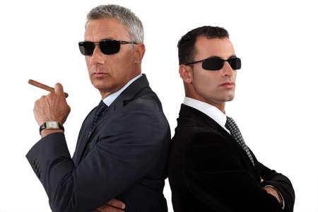 garde corps: Hommes d'affaires puissants dans des lunettes de soleil Banque d'images