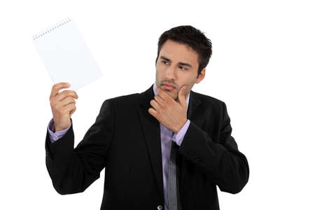 curiously: Businessman looking at notepad curiously