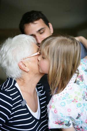 mom kiss son: Child kissing her grandma