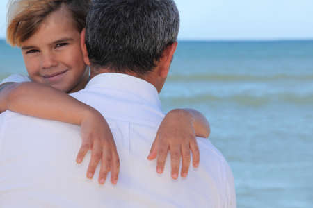 A father hugging his son on the beach. photo