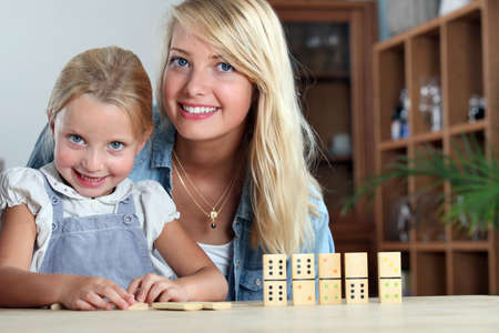 Mother and daughter playing dominoes photo