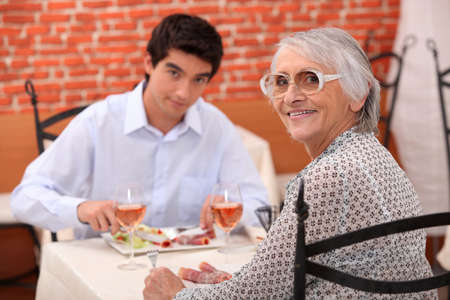 adult 80s: Young man and elderly woman in a restaurant